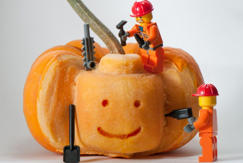a pumpkin being carved by Lego construction workers