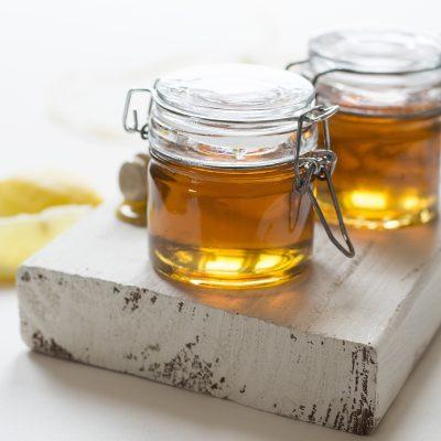 two jars of honey on wood plank
