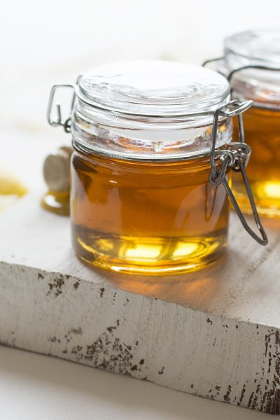 two jars of honey on wood plank