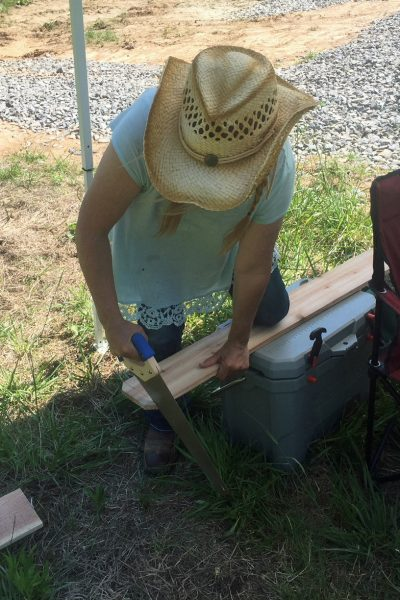 Niki Dee sawing a cedar plank 5 dog farm